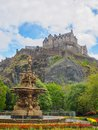 Edinburgh Castle and Ross Fountain seen from the Princes Street Gardens on a bright sunny day. Royalty Free Stock Photo