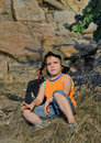 Educated little boy during a hiking expedition caucasian cute sitting on the ground next to his backpack in sunny day of summer Stock Photography
