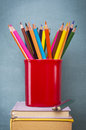 Education books penholder and colorful pencils in front of green chalkboard Royalty Free Stock Image