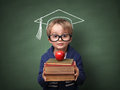 Education child holding stack of books with mortar board chalk drawing on blackboard concept for university and future aspirations Royalty Free Stock Images