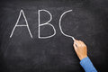 Education concept abc alphabet school blackboard teacher writing in english class or preschool on Stock Photos