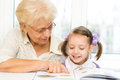 Education concept grandmother teaches to read a book her granddaughter Stock Photos