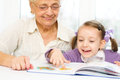 Education concept grandmother teaches to read a book her granddaughter Royalty Free Stock Photography