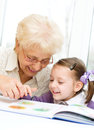 Education concept grandmother teaches to read a book her granddaughter Stock Images