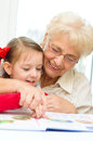 Education concept grandmother teaches to read a book her granddaughter Stock Photo