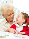 Education concept grandmother teaches to read a book her granddaughter Royalty Free Stock Photos