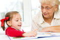 Education concept grandmother teaches to read a book her granddaughter Stock Image