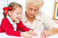 Education concept grandmother teaches to read a book her granddaughter Royalty Free Stock Photo