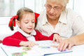 Education concept grandmother teaches to read a book her granddaughter Stock Photography