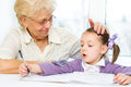 Education concept grandmother teaches to write letters her granddaughter Royalty Free Stock Photo