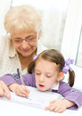 Education concept grandmother teaches to write letters her granddaughter Royalty Free Stock Photography