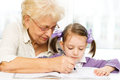 Education concept grandmother teaches to write letters her granddaughter Stock Image