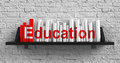 Education concept red inscription on the books on shelf on the white brick wall background Stock Photo