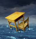 Education problems concept with an old school desk drowning in the water during a storm as a symbol of inaccessible schooling and Stock Photography