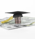 Education savings mortar board on a stack of quarters and one hundred dollar bills Royalty Free Stock Photo
