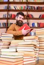 Education and science concept. Teacher or student with beard studying in library between piles of books. Man on smiling Royalty Free Stock Photo