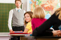 Education teacher with pupil in school teaching young his form of the elementary or primary Royalty Free Stock Images