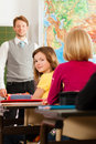 Education teacher with pupil in school teaching young his form of the elementary or primary Royalty Free Stock Photo