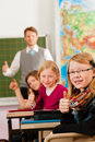Education teacher with pupil in school teaching young his form of the elementary or primary Stock Images