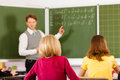 Education teacher with pupil in school teaching young his form of the elementary or primary Royalty Free Stock Image