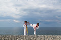 The education of the two children on the beach: Taekwondo, sport Royalty Free Stock Photo