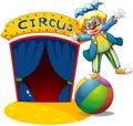 Een clown bij de bovenkant van de bal naast een circushuis Stock Afbeeldingen
