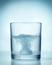 Effervescent dissolving fizzy tablet in water glass Royalty Free Stock Image