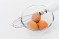Egg beater with eggs on a glass bowl Royalty Free Stock Photos