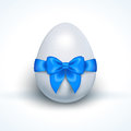 Egg with blue ribbon bow isolated on white