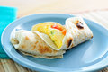 Egg burrito with tomatoes and green onion an scrambled breakfast cheese Stock Photos