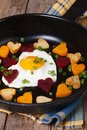 Egg in the form of heart in a pan with vegetables closeup vertical Royalty Free Stock Photography