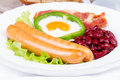 Egg fried in green pepper sausages bacon and red beans a Stock Photos
