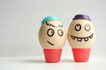 Egg with painted face. Two eggs in caps Royalty Free Stock Photo