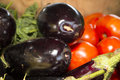 Egg plant and tomatoes at farmers market in grand haven michigan in a bushels green leaves in background Royalty Free Stock Image