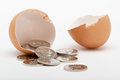 Egg shell and coins falling out of on white background Royalty Free Stock Photo