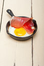 Egg sunny side up with italian speck ham fried tyrolean smoked on a skillet Royalty Free Stock Photo