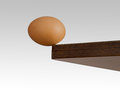 Egg teetering on the edge brink real risk danger concept or metaphor Royalty Free Stock Images