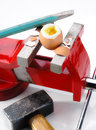 Egg vise chisel and hammer an gripped in the broken by a pieces of broken eggshell are around Royalty Free Stock Photography