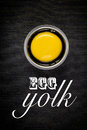 Egg yolk on black with text Stock Images