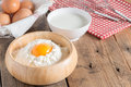 Egg yolk in the flour with milk and whip for beating on wood tab Royalty Free Stock Photo