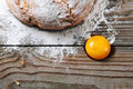 Egg yolk wooden table sprinkled with flour on the table lay freshly baked bread and an ingredients for making bread rural style Stock Photography