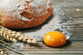 Egg yolk wooden table sprinkled with flour on the table lay spikelets of wheat freshly baked bread and an ingredients for making Stock Photography