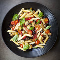 Eggplant chilli and tomato pasta penne on a black serving platter garnished with basil Royalty Free Stock Image