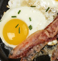 Eggs and bacon fried in a skillet Stock Photos