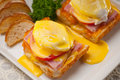 Eggs benedict on bread with tomato and ham Royalty Free Stock Photo