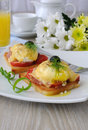 Eggs benedict with ham and tomato and cheese on toast with orange juice and coffee Stock Photo