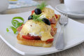 Eggs benedict with ham and tomato on toast with cheese olives Royalty Free Stock Photography