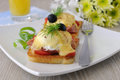 Eggs benedict with ham and tomato on toast with cheese orange juice Stock Photography