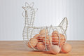 Eggs and chicken wire egg basket full or organic brown in a country kitchen Royalty Free Stock Images