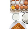 Eggs, glass of milk, flour and baked goods Stock Photography
